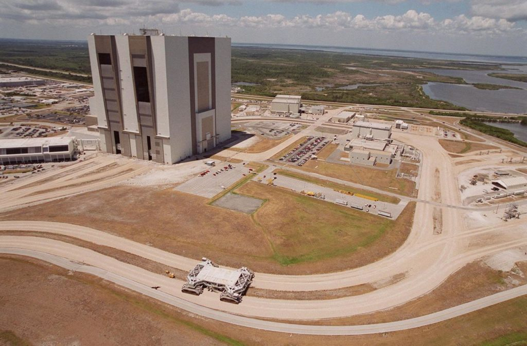 This aerial photo captures many of the facilities involved in Space Shuttle processing. At center is the Vehicle Assembly Building (VAB). The curved road in the foreground is the newly restored crawlerway leading into the VAB high bay 2. The road restoration and high bay 2 are part of KSC's Safe Haven project, enabling the storage of orbiters during severe weather. The road circles around the Orbiter Processing Facility 3 (OPF-3) at right center. OPF1 and OPF-2 are just above the curving road. On the left of the VAB, the crawlerway also extends from high bays 1 and 3, past the Launch Control Center, out to the two Shuttle launch pads KSC00pp0733