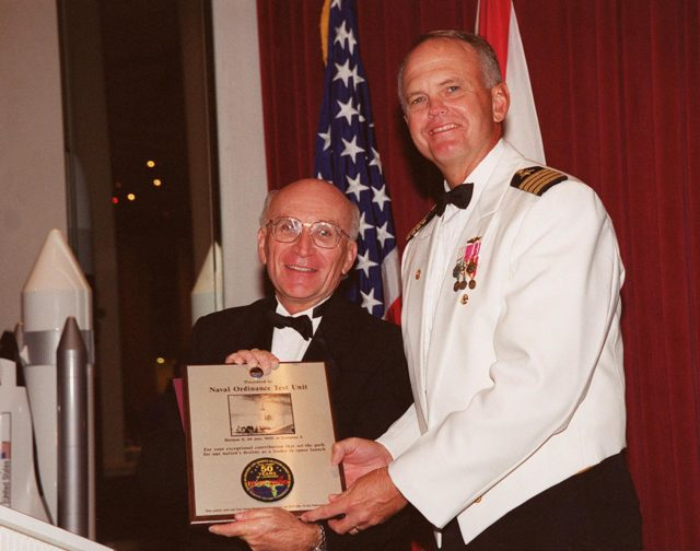 At the 50th anniversary gala that capped a year-long celebration of 50 years of rocket launches from Cape Canaveral Air Force Station, gala chairman Ed Gormel (left) presents a plaque to Capt. Harry Sheffield, Commander, Naval Ordnance Test Unit, Cape Canaveral. The first launch at CCAFS took place at 9:28 a.m. on July 24, 1950, with the liftoff of Bumper 8 from Launch Complex 3. The gala was hosted by the Cape Canaveral Chapter Air Force Association KSC-00pp0932