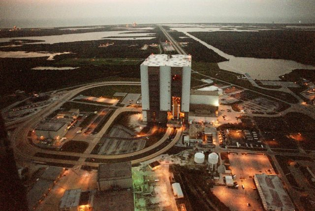 """KENNEDY SPACE CENTER, FLA. -- At 6:30 a.m. EDT an aerial view captures a first in Space Shuttle history: a fully stacked Shuttle - Atlantis - is rolling into the Vehicle Assembly Building's (VAB) high bay 2 on the building's west side (center of photo).  The VAB and nearby rock-paved crawlerway (circling to the left) have recently undergone major modifications to provide Shuttle fliglht hardware more storage space and protection - """"Safe Haven"""" - from hurricanes or tropical storms.  Atlantis, the twin solid rocket boosters and external tank begain moving out of VAB high bay 1 on the east side at 2:59 a.m. EDT.  The 6-million pound crawler transporter carried the Mobile Launcher Platform and Space Shuttle around the north side of the VAB and into high bay 2.  To the right of the VAB is the turn basin.  In the background can be seen both Launch Pads with the Atlantic Ocean behind them.  After the successful """"Safe Haven"""" fit check, Shuttle Atlantis is scheduled to roll out to Launch Pad 39B in preparation for the STS-106 launch on Sept. 8. KSC-00pp1109"""