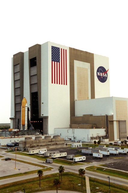 """KENNEDY SPACE CENTER, FLA. -- For the first time in Space Shuttle history, a fully stacked Shuttle - Atlantis - is rolling into the Vehicle Assembly Building's (VAB) high bay 2 on the building's west side.  The VAB and nearby rock-paved crawlerway have recently undergone major modifications to provide Shuttle fliglht hardware more storage space and protection - """"Safe Haven"""" - from hurricanes or tropical storms.  Atlantis, the twin solid rocket boosters and external tank begain moving out of VAB high bay 1 on the east side at 2:59 a.m. EDT.  The 6-million pound crawler transporter carried the Mobile Launcher Platform and Space Shuttle around the north side of the VAB and into high bay 2.  After the successful """"Safe Haven"""" fit check, Shuttle Atlantis is scheduled to roll out to Launch Pad 39B in preparation for the STS-106 launch on Sept. 8. KSC-00pp1110"""