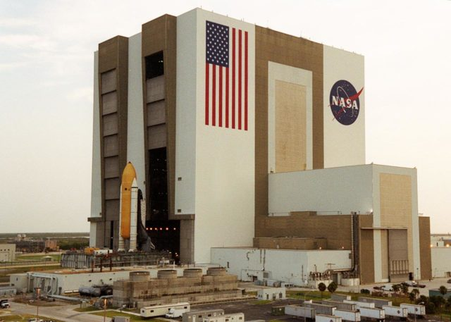 """KENNEDY SPACE CENTER, FLA. -- Just after sunup, Shuttle Atlantis sits outside the Vehicle Assembly Building's (VAB) high bay 2 on the building's west side after completing a fit check.  This is the first time in Space Shuttle history that a fully stacked Shuttle is being moved into the space. The VAB and nearby rock-paved crawlerway have recently undergone major modifications to provide Shuttle fliglht hardware more storage space and protection - """"Safe Haven"""" - from hurricanes or tropical storms.  Atlantis, the twin solid rocket boosters and external tank begain moving out of VAB high bay 1 on the east side at 2:59 a.m. EDT.  The 6-million pound crawler transporter carried the Mobile Launcher Platform and Space Shuttle around the north side of the VAB and into high bay 2.  After the successful """"Safe Haven"""" fit check, Shuttle Atlantis is scheduled to roll out to Launch Pad 39B in preparation for the STS-106 launch on Sept. 8. KSC-00pp1111"""