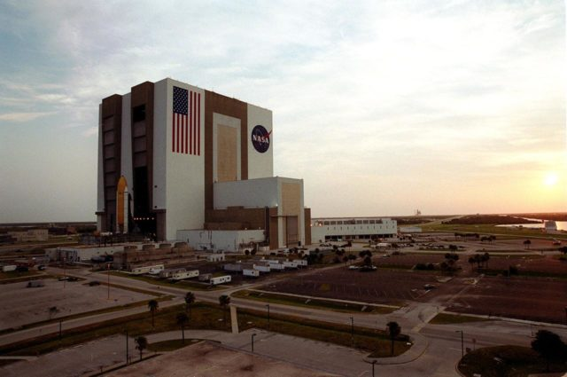 """KENNEDY SPACE CENTER, FLA. -- The sun is rising over the Atlantic Ocean (right) as Shuttle Atlantis sits outside the Vehicle Assembly Building's (VAB) high bay 2 on the building's west side after completing a fit check.  This is the first time in Space Shuttle history that a fully stacked Shuttle has been moved into the space. The VAB and nearby rock-paved crawlerway have recently undergone major modifications to provide Shuttle fliglht hardware more storage space and protection - """"Safe Haven"""" - from hurricanes or tropical storms.  Atlantis, the twin solid rocket boosters and external tank begain moving out of VAB high bay 1 on the east side at 2:59 a.m. EDT.  The 6-million pound crawler transporter carried the Mobile Launcher Platform and Space Shuttle around the north side of the VAB and into high bay 2.  After the successful """"Safe Haven"""" fit check, Shuttle Atlantis is scheduled to roll out to Launch Pad 39B in preparation for the STS-106 launch on Sept. 8. KSC-00pp1112"""