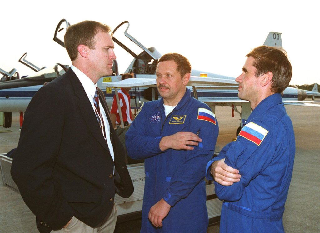 """Jim Halsell Jr. (left), former mission commander and now the manager, Shuttle Program Integration Office, chats with STS-106 Mission Specialists Boris V. Morukov (center) and Yuri I. Malenchenko (right) after their arrival at KSC. Morukov and Malenchenko, who are with the Russian Aviation and Space Agency, are at KSC with the rest of the crew to take part in Terminal Countdown Demonstration Test activities, which include emergency egress training and a simulated launch countdown. STS-106 is scheduled to launch Sept. 8, 2000, at 8:31 a.m. EDT from Launch Pad 39B. On the 11-day mission, the seven-member crew will perform support tasks on orbit, transfer supplies and prepare the living quarters in the newly arrived Zvezda Service Module. The first long-duration crew, dubbed """"Expedition One,"""" is due to arrive at the Station in late fall KSC00pp1133"""