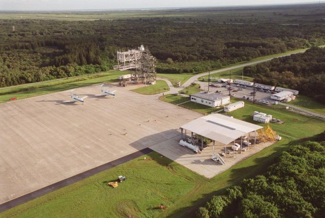KENNEDY SPACE CENTER, FLA. -- This aerial view of the Shuttle Landing Facility (SLF) faces northeast, with the Atlantic Ocean in the distance. In the center is the apron of the SLF with two Shuttle Training Aircraft (STA) parked there, the mate/demate device behind them, a shelter for fuel trucks (foreground), and an administrative building between. The STAs are Grumman Gulfstream 2 aircraft with converted cockpits that emulate those in the Shuttles for practice landings at the SLF. The mate/demate device is used to lift the orbiter onto or off a Shuttle Carrier Aircraft when it has to be ferried to or from KSC KSC-00pp1431