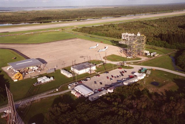 KENNEDY SPACE CENTER, FLA. -- An aerial view of the Shuttle Landing Facility shows the fuel truck shelter (left), administrative building (center) with parking lot behind it (foreground), two Shuttle Training Aircraft (STA) parked on the apron and the mate/demate device (right). In the background is the runway. The STAs are Grumman Gulfstream 2 aircraft with converted cockpits that emulate those in the Shuttles for practice landings at the SLF. The mate/demate device is used to lift the orbiter onto or off a Shuttle Carrier Aircraft when it has to be ferried to or from KSC KSC00pp1430