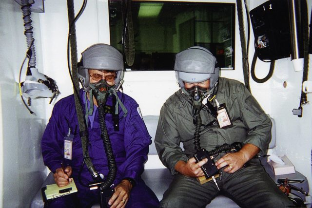 Jan Zysko (left) and Rich Mizell (right) test a Personal Cabin Pressure Altitude Monitor in an altitude chamber at Tyndall Air Force Base in Florida. Zysko invented the pager-sized monitor that alerts wearers of a potentially dangerous or deteriorating cabin pressure altitude condition, which can lead to life-threatening hypoxia. Zysko is chief of the KSC Spaceport Engineering and Technology directorate's data and electronic systems branch. Mizell is a Shuttle processing engineer. The monitor, which has drawn the interest of such organizations as the Federal Aviation Administration for use in commercial airliners and private aircraft, was originally designed to offer Space Shuttle and Space Station crew members added independent notification about any depressurization KSC00padig049