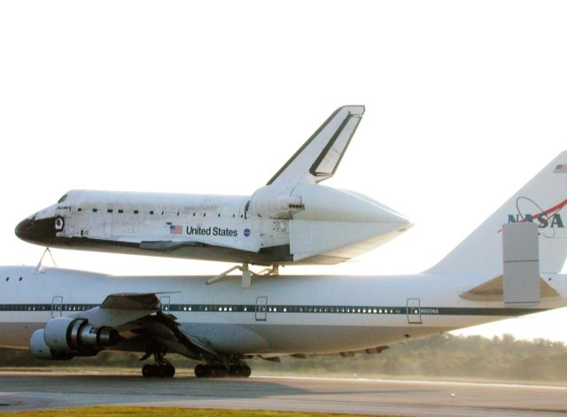 In the glow of a late afternoon sun, the Shuttle Carrier Aircraft (SCA) returns the orbiter Discovery to KSC after the orbiter's California landing at Edwards Air Force Base at the end of mission STS-92. Discovery wears a tail cone protecting its aft nozzles for the ferry flight. Discovery will be demated from the SCA via the mate/demate device at the SLF and transported to the Orbiter Processing Facility bay 1. There it will undergo preparations for its next launch, STS-102, scheduled for February 2001 KSC-00padig078