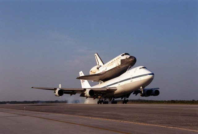 Kicking up dust, the Shuttle Carrier Aircraft, with its unique cargo on top, touches down on runway 33 at the Shuttle Landing Facility. The ferry flight started in California after the orbiter's landing more than a week ago at Edwards Air Force Base at the end of mission STS-92. Discovery will be demated from the SCA via the mate/demate device at the SLF and transported to the Orbiter Processing Facility bay 1. There it will undergo preparations for its next launch, STS-102, scheduled for February 2001 KSC-00pp1642