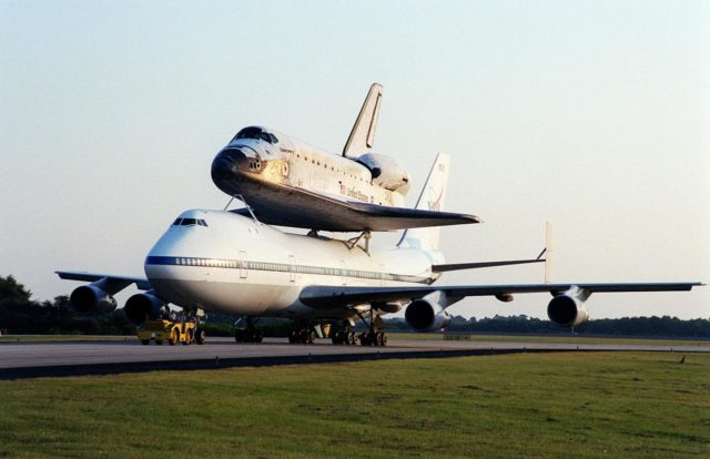 After landing at the Shuttle Landing Facility (SLF), the Shuttle Carrier Aircraft (SCA), with its unique cargo Discovery on top, is towed to the mate/demate device at the SLF. Discovery will be lifted off the SCA and transported to the Orbiter Processing Facility bay 1. There it will undergo preparations for its next launch, STS-102, scheduled for February 2001 KSC-00pp1643