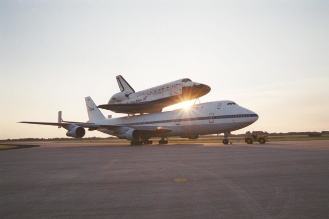 After landing at the Shuttle Landing Facility (SLF), the Shuttle Carrier Aircraft (SCA), with its unique cargo Discovery on top, is towed to the mate/demate device at the SLF. Discovery will be lifted off the SCA and transported to the Orbiter Processing Facility bay 1. There it will undergo preparations for its next launch, STS-102, scheduled for February 2001 KSC-00pp1644