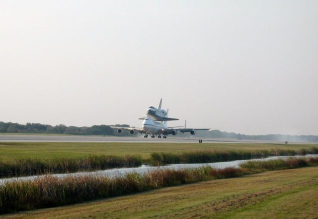 In the soft glow of a soon-to-set sun, the Shuttle Carrier Aircraft (SCA), with its unique orbiter passenger attached to its back, gently touches down on the runway at KSC's Shuttle Landing Facility. The SCA is returning Discovery to KSC after the orbiter's California landing at Edwards Air Force Base at the end of mission STS-92. Discovery will be demated from the SCA via the mate/demate device at the SLF and transported to the Orbiter Processing Facility bay 1. There it will undergo preparations for its next launch, STS-102, scheduled for February 2001 KSC00padig076