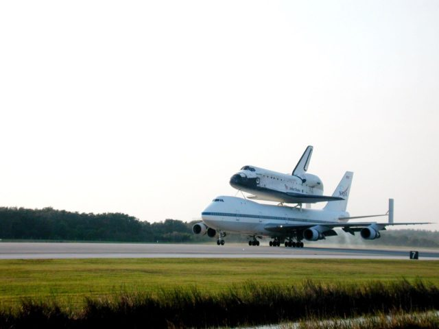 On a warm afternoon, the Shuttle Carrier Aircraft (SCA), with its unique orbiter passenger attached to its back, rolls down the runway at KSC's Shuttle Landing Facility. The SCA is returning Discovery to KSC after the orbiter's California landing more than a week ago at Edwards Air Force Base at the end of mission STS-92. Discovery will be demated from the SCA via the mate/demate device at the SLF and transported to the Orbiter Processing Facility bay 1. There it will undergo preparations for its next launch, STS-102, scheduled for February 2001 KSC00padig077