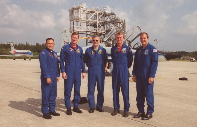 After their arrival at the Shuttle Landing Facility, the STS-97 crew pose for a photo on the parking area. Behind them are the T-38 jet aircraft that brought them. From left, they are Mission Specialist Carlos Noriega, Joe Tanner and Marc Garneau (with the Canadian Space Agency); Commander Brent Jett; and Pilot Mike Bloomfield. The crew is at KSC to take part in Terminal Countdown Demonstration Test activities that include emergency egress training, familiarization with the payload, and a simulated launch countdown. In the background, top, is the mate/demate device that is used to load or unload an orbiter from the back of the Shuttle Carrier Aircraft. In the background left is a Shuttle Training Aircraft. Mission STS-97is the sixth construction flight to the International Space Station. Its payload includes the P6 Integrated Truss Structure and a photovoltaic (PV) module, with giant solar arrays that will provide power to the Station. The mission includes two spacewalks to complete the solar array connections. STS-97 is scheduled to launch Nov. 30 at about 10:05 p.m. EST KSC00pp1641