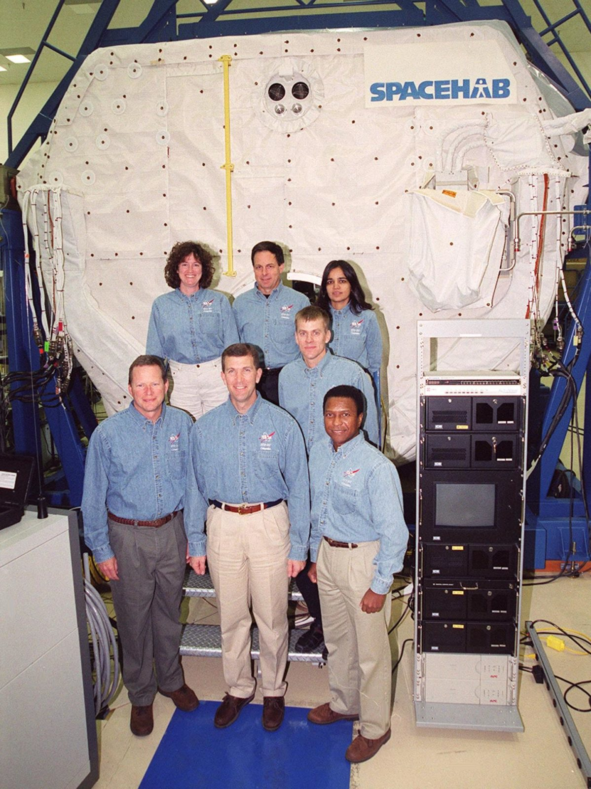 """KENNEDY SPACE CENTER, Fla. -- Taking part in In-Flight Maintenance training, the STS-107 crew poses in front of the SPACEHAB Double Module. In back are Mission Specialist Laurel Clark, Payload Specialist Ilan Ramon of Israel, and Mission Specialist Kalpana Chawla; in front are Mission Specialist David M. Brown, Commander Rick D. Husband, Pilot William C. """"Willie"""" McCool (behind) and Mission Specialist Michael Anderson. As a research mission, STS-107 will carry the SPACEHAB Double Module in its first research flight into space and a broad collection of experiments ranging from material science to life science. It is scheduled to launch July 19, 2001 KSC-00pp1852"""