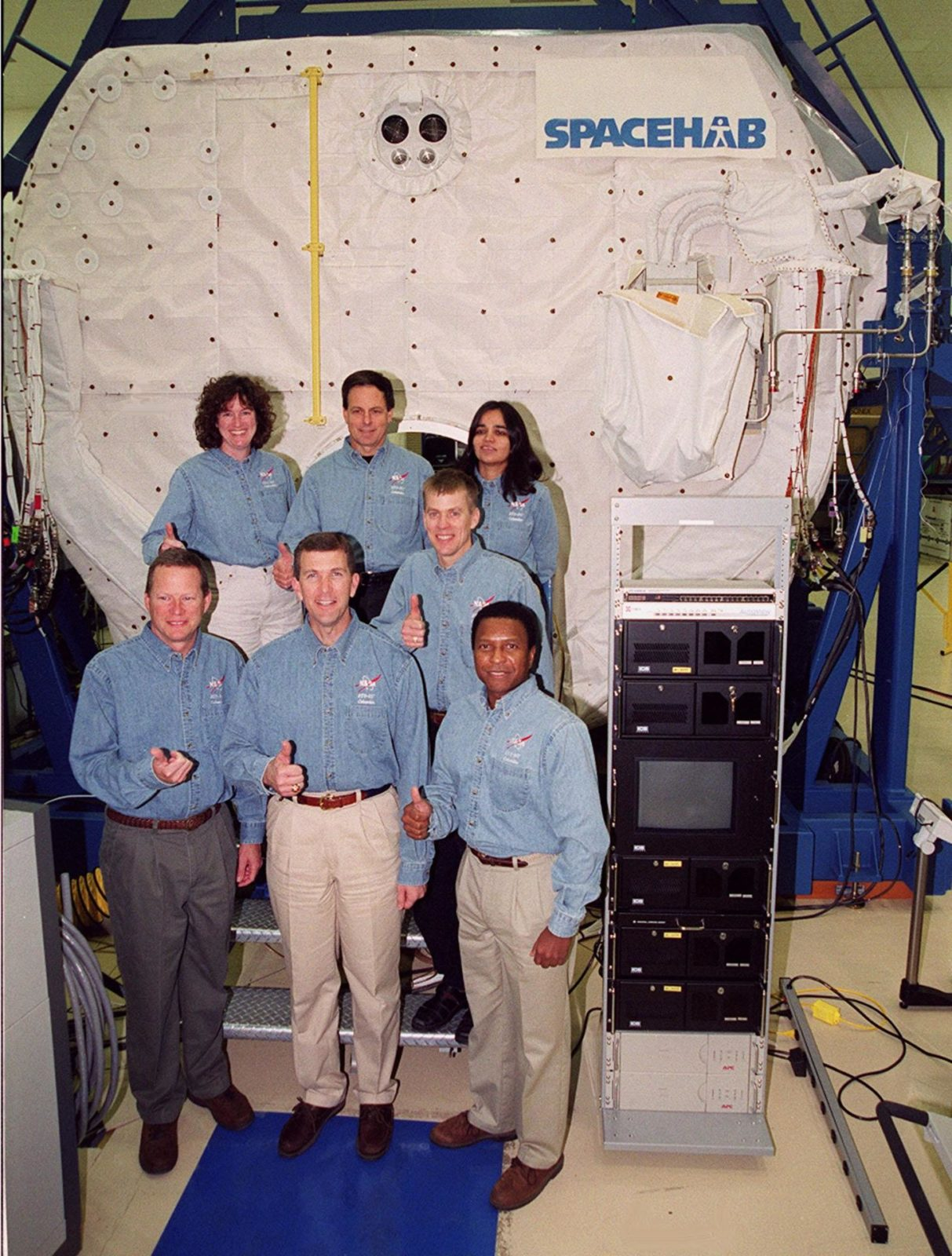 """KENNEDY SPACE CENTER, Fla. -- Taking part in In-Flight Maintenance training, the STS-107 crew poses in front of the SPACEHAB Double Module. In back are Mission Specialist Laurel Clark, Payload Specialist Ilan Ramon of Israel and Mission Specialist Kalpana Chawla; in front are Mission Specialist David M. Brown, Commander Rick D. Husband, Pilot William C. """"Willie"""" McCool (behind) and Mission Specialist Michael Anderson. As a research mission, STS-107 will carry the SPACEHAB Double Module in its first research flight into space and a broad collection of experiments ranging from material science to life science. It is scheduled to launch July 19, 2001 KSC00pp1853"""