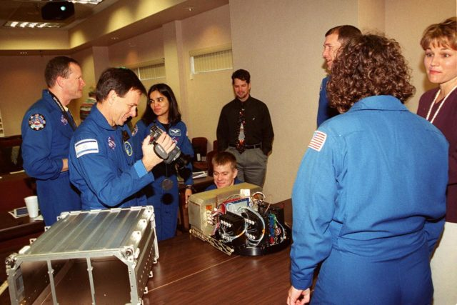 """KENNEDY SPACE CENTER, FLA. -- As part of In-Flight Maintenance training, members of the STS-107 crew check out one of the Biotube experiments that will be part of their research mission . From left (in uniform) are Mission Specialist David M. Brown, Payload Specialist Ilan Ramon of Israel, and Mission Specialist Kalpana Chawla; Pilot William C. """"Willie"""" McCool (crouching behind the table); Commander Rick D. Husband; and Mission Specialist Laurel Clark. At right is project engineer April Boody. As a research mission, STS-107 will carry the SPACEHAB Double Module in its first research flight into space and a broad collection of experiments ranging from material science to life science. It is scheduled to launch July 19, 2001 KSC-00pp1846"""