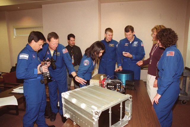 """KENNEDY SPACE CENTER, FLA. -- As part of In-Flight Maintenance training, members of the STS-107 crew check out one of the Biotube experiments that will be part of their research mission. From left (in uniform) are Payload Specialist Ilan Ramon of Israel, Mission Specialists David M. Brown and Kalpana Chawla, Pilot William C. """"Willie"""" McCool (crouching behind the table), Commander Rick D. Husband, and Mission Specialist Laurel Clark. STS-107 will carry the SPACEHAB Double Module in its first research flight into space and a broad collection of experiments ranging from material science to life science. It is scheduled to launch July 19, 2001 KSC-00pp1847"""