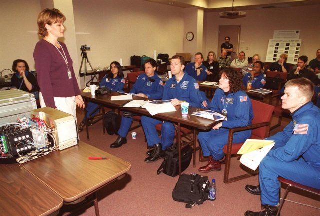 """KENNEDY SPACE CENTER, FLA. -- The STS-107 crew takes part in In-Flight Maintenance training, learning more about experiments that will be part of the mission. Seated in front (left to right) are Mission Specialist Kalpana Chawla, Payload Specialist Ilan Ramon of Israel; Commander Rick D. Husband; Mission Specialist Laurel Clark; and Pilot William C. """"Willie"""" McCool; in back are Mission Specialists David M. Brown and Michael Anderson. As a research mission, STS-107 will carry the SPACEHAB Double Module in its first research flight into space and a broad collection of experiments ranging from material science to life science. It is scheduled to launch July 19, 2001 KSC-00pp1851"""