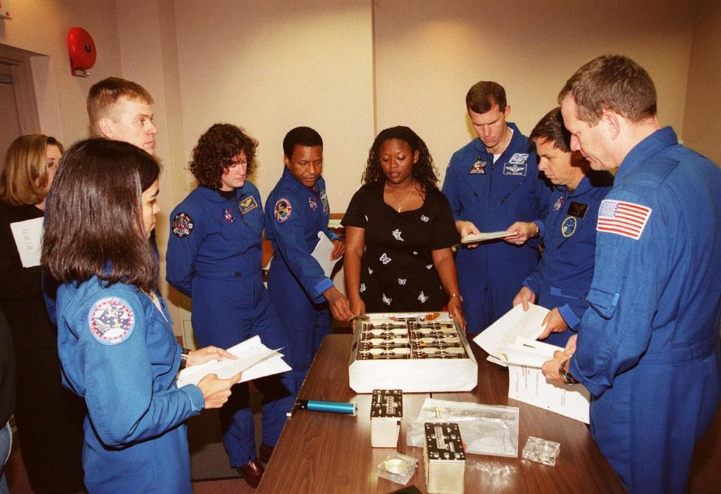 """As part of In-Flight Maintenance training at SPACEHAB, in Cape Canaveral, Fla., members of the STS-107 crew learn about Biological Research in Canisters (BRIC) experiments that will be on their mission. Gathered around the table are (from left) Mission Specialist Kalpana Chawla, Pilot William C. """"Willie"""" McCool, Mission Specialists Laurel Clark and Michael Anderson, Roberteen McCray of Bionetics, Commander Rick D. Husband, Payload Specialist Ilan Ramon of Israel and Mission Specialist David M. Brown. STS-107 will carry a broad collection of experiments ranging from material science to life science. It is scheduled to launch July 19, 2001 KSC-00pp1856"""