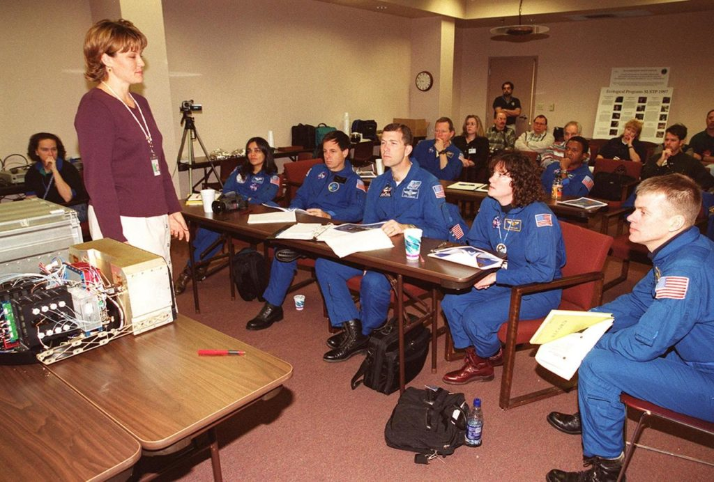 """KENNEDY SPACE CENTER, FLA. -- The STS-107 crew takes part in In-Flight Maintenance training, learning more about experiments that will be part of the mission. Seated in front (left to right) are Mission Specialist Kalpana Chawla, Payload Specialist Ilan Ramon of Israel; Commander Rick D. Husband; Mission Specialist Laurel Clark; and Pilot William C. """"Willie"""" McCool; in back are Mission Specialists David M. Brown and Michael Anderson. As a research mission, STS-107 will carry the SPACEHAB Double Module in its first research flight into space and a broad collection of experiments ranging from material science to life science. It is scheduled to launch July 19, 2001 KSC00pp1851"""