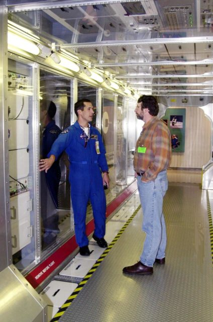 """KENNEDY SPACE CENTER, FLA. -- Astronaut John Herrington (left) shows a mockup of the U.S. Lab to Norm Abram, master carpenter of television's  """"This Old House"""" and """"The New Yankee Workshop."""" Abram is at KSC to film an episode of """"This Old House."""" The mockup lab is in the International Space Station Center, a tour facility KSC-00padig121"""