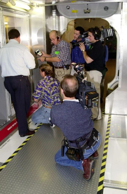 """KENNEDY SPACE CENTER, FLA. -- A film crew gather around Steve Thomas (kneeling) as they shoot inside a mockup of the U.S. Lab, located in the International Space Station Center, a tour facility. Thomas and Norm Abram, host and master carpenter, respectively, of television's  """"This Old House,"""" are at KSC to film an episode of the series KSC-00padig124"""
