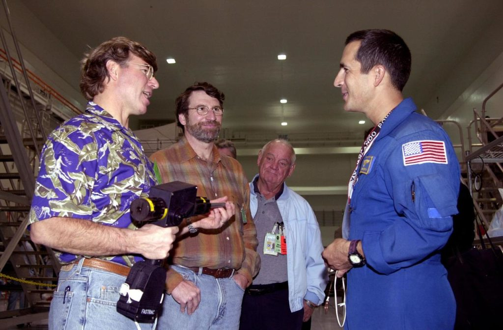 "KENNEDY SPACE CENTER, FLA. -- Steve Thomas (left) and Norm Abram (second from left), who are seen in the television series ""This Old House,"" talk with astronaut John Herrington (right). In the background is Johnny Johnson, media escort. Abram is at KSC to film an episode of ""This Old House. KSC-00padig125"
