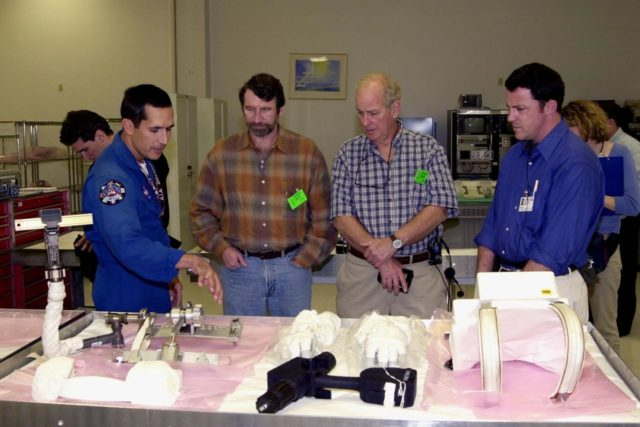 """KENNEDY SPACE CENTER, FLA. -- Astronaut John Herrington (left) shows tools and equipment used in space to Norm Abram, master carpenter of television's """"This Old House"""" and """"The New Yankee Workshop."""" At right are two of the film crew with Abram. Abram is at KSC to film an episode of """"This Old House. KSC-00padig127"""