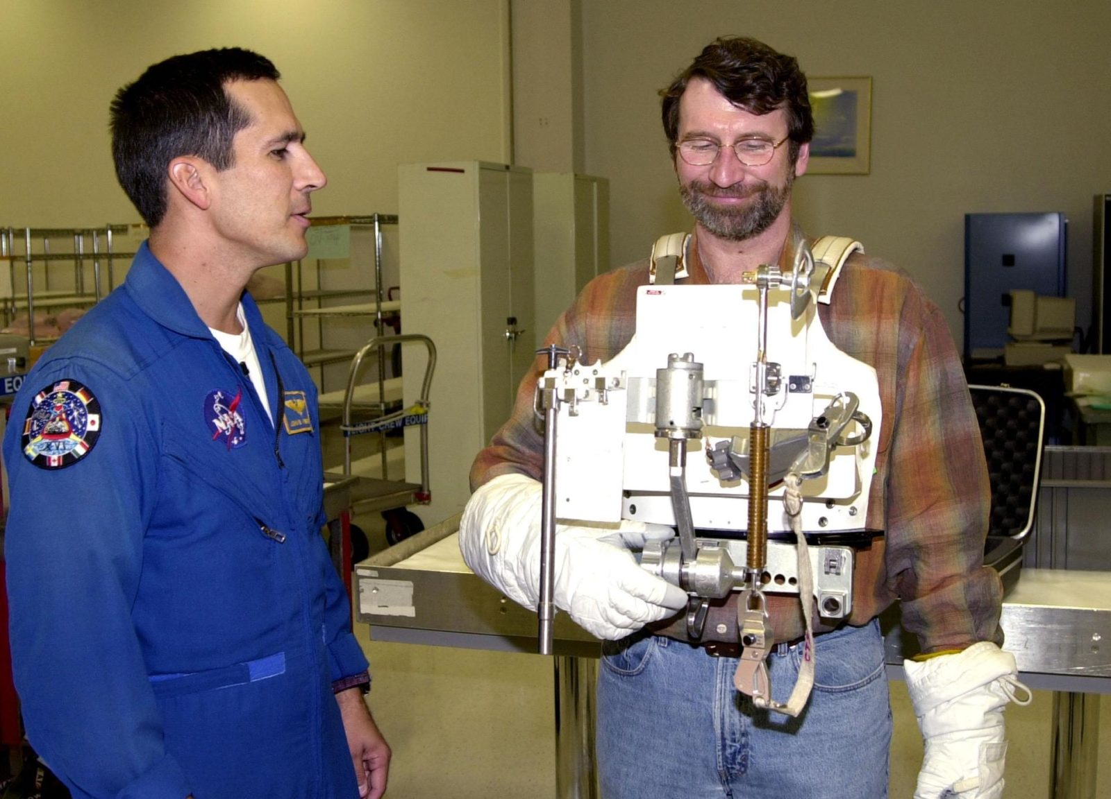 """KENNEDY SPACE CENTER, FLA. -- While astronaut John Herrington (left) looks on, Norm Abram tries on a tool carrier used in space. Abram is master carpenter of television's """"This Old House"""" and """"The New Yankee Workshop."""" He is at KSC to film an episode of """"This Old House. KSC-00padig128"""