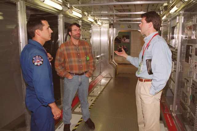 """KENNEDY SPACE CENTER, FLA. --  Astronaut John Herrington (left) and Norm Abram, of television's """"This Old House"""" and """"The New Yankee Workshop,"""" talk to Phil West, of Johnson Space Center. They are standing in front of a mockup of the U.S. Lab, located in the International Space Station Center, a tour facility.. Abram is at KSC to film an episode of """"This Old House. KSC-00pp1914"""