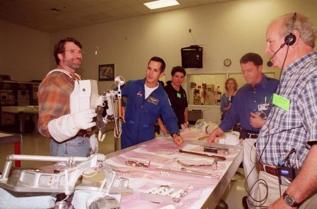"""KENNEDY SPACE CENTER, FLA. --  Norm Abram, of television's """"This Old House"""" and """"The New Yankee Workshop,"""" looks at tools and equipment used in space while astronaut John Herrington (second from left) watches. At right are two of the film crew with Abram. Abram is at KSC to film an episode of """"This Old House. KSC-00pp1915"""