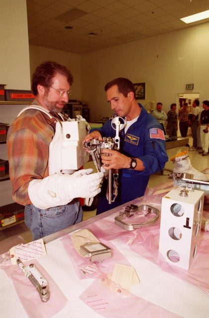 """KENNEDY SPACE CENTER, FLA. --  Astronaut John Herrington (right) helps Norm Abram try on a tool carrier used in space. Abram is the master carpenter on television's """"This Old House.""""  He is at KSC to film an episode of the series KSC-00pp1916"""