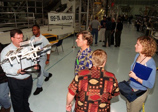"""KENNEDY SPACE CENTER, FLA. --  In the Space Station Processing Facility, Steve Thomas (center), looks at a model of the International Space Station being held by a worker. Thomas is host of the television series """"This Old House."""" In the foreground and at right are crew members of the television series.; They are at KSC to film an episode of the series KSC-00pp1918"""