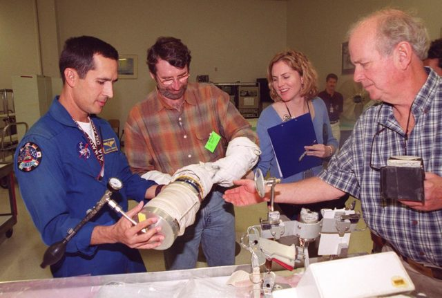 """KENNEDY SPACE CENTER, FLA. --  Astronaut John Herrington (left) shows tools and equipment used in space to Norm Abram, master carpenter of television's """"This Old House"""" and """"The New Yankee Workshop.""""  At right are two of the film crew with Abram. Abram is at KSC to film an episode of """"This Old House. KSC-00pp1926"""
