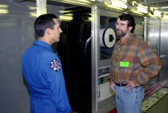 """KENNEDY SPACE CENTER, FLA. -- Astronaut John Herrington (left) and Norm Abram, master carpenter of television's """"This Old House"""" and """"The New Yankee Workshop,"""" talk in front of a mockup of the U.S. Lab. Abram is at KSC to film an episode of """"This Old House."""" The mockup lab is in the International Space Station Center, a tour facility KSC00padig122"""