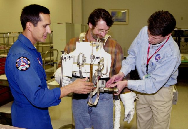 """KENNEDY SPACE CENTER, FLA. -- After trying on a tool carrier, master carpenter of television's """"This Old House"""" and """"The New Yankee Workshop"""" Norm Abram (center) receives assistance from astronaut John Herrington (left) and Phil West (right), with Johnson Space Center. Abram is at KSC to film an episode of """"This Old House. KSC00padig129"""
