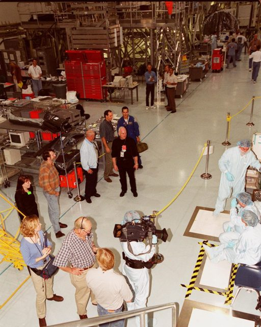 """KENNEDY SPACE CENTER, FLA. -- Master Carpenter Norm Abram and crew of the television series """"This Old House"""" stop in the Space Station Processing Facility on their tour of KSC. Abram is at left center. Escorting them is Bill Johnson (center, in the aisle), NASA TV manager; accompanying them is astronaut John Herrington (behind Johnson). Abram is at KSC to film an episode of the series KSC00pp1921"""