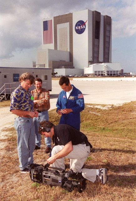 Across from the Vehicle Assembly Building and Launch Control Center, Steve Thomas (left), host of This Old House, and Norm Abram (second from left), master carpenter on the series, watch as a a videographer (in front) checks his camera. With them is astronaut John Herrington. The cast and crew of This Old House are filming at KSC for an episode of the show. Herrington is accompanying the film crew on their tour of KSC KSC00pp1958