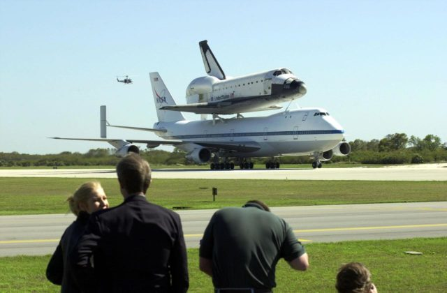 KENNEDY SPACE CENTER, FLA. -- Media (foreground) capture the orbiter Columbia atop a Shuttle Carrier Aircraft as it taxis down the runway. A helicopter hovers in the background. The SCA and its cargo landed at the Cape Canaveral Air Force Station Skid Strip. The ferry flight began in California March 1. Unfavorable weather conditions kept it on the ground at Dyess AFB, Texas, until it could return to Florida. Columbia is returning from a 17-month-long modification and refurbishment process as part of a routine maintenance plan. The orbiter will next fly on mission STS-107, scheduled Oct. 25 KSC01padig128
