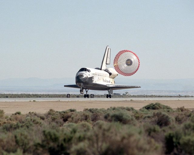 NASA/EDWARDS AFB, CALIF. -- With its drag chute deployed, Endeavour lands on runway 22 at Edwards Air Force Base, Calif., at 12:10:42 p.m. EDT after a mission of 11 days, 12 hours, 54 minutes to the International Space Station on mission STS-100. The orbiter and its crew of seven logged about 4.9 million statute miles in 186 orbits. Due to unfavorable weather conditions, landing at KSC was waved off. The landing marked the third consecutive landing at EAFB. KSC-01PP0948