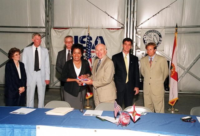KENNEDY SPACE CENTER, Fla. -- After the signing of a lease agreement between Spaceport Florida Authority (SFA) and United Space Alliance (USA) for the use of a hangar at Kennedy Space Center, (foreground left) Marcie Harris, USA site director, and (foreground right) Ed Gormel, Spaceport Florida executive director, hold a symbolic ribbon. Behind them are (left to right) Rochelle Cooper, USA associate general counsel; Marv Jones, KSC associate director; Greg Popp, Spaceport Florida business manager; Congressman Dave Weldon; and State Rep. Mike Haridopolos. The hangar was originally developed by the state as part of a joint NASA/SFA Reusable Launch Vehicle Support Complex at KSC. USA plans to use the state-developed 50,000-square-foot facility to store and maintain Space Shuttle ground equipment KSC-01pp1269