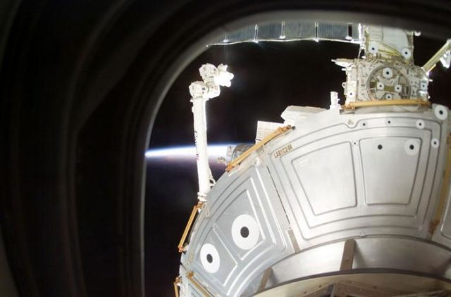 SSRMS/Canadarm2 and ISS backdropped by Earth limb