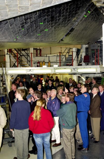 KENNEDY SPACE CENTER, FLA. --  In the Orbiter Processing Facility, former President Jimmy Carter (center) gets a closeup view of the underside of an orbiter space vehicle.  On the outer edge of the crowd are (left to riht) Launch Director Mike Leinbach (green jacket), Space Shuttle Launch Integration Manager Jim Halsell and Center Director Roy D. Bridges.  Carter and former First Lady Rosalyn Carter are touring KSC KSC-02pd0013