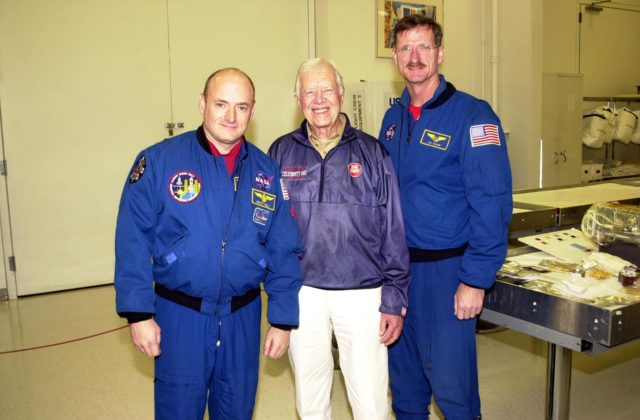 KENNEDY SPACE CENTER, FLA. --  In the Space Station Processing Facility, former President Jimmy Carter (center) pauses for a photo with astronauts Scott Kelly (left) and Joseph Tanner (right). Carter and former First Lady Rosalyn Carter are touring KSC KSC-02pd0014