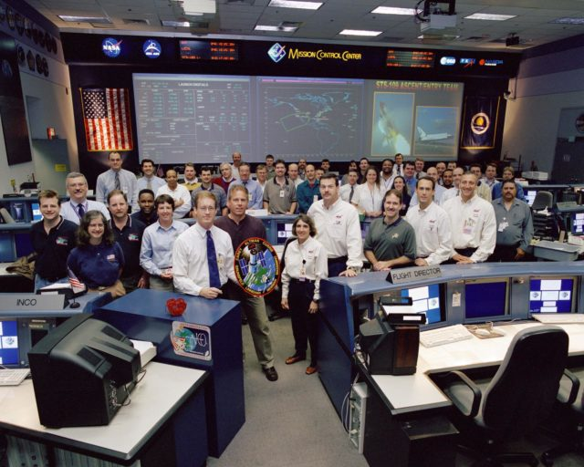 JSC2002-00514 (February 2002)--- The STS-109 flight crew poses with the ascent and entry shift team in the Shuttle Flight Control Room of the Johnson Space Center's Mission Control Center.  Flight Director John Shannon holds the mission insignia.  Members of the flight crew are astronauts Scott D. Altman, commander; Duane G. Carey, pilot; John M. Grunsfeld, payload commander; and James H. Newman, Nancy J. Currie, Richard M. Linnehan and Michael J. Massimino, all mission specialists.  Currie stands to the right of the logo, followed  by, left to right,  Altman, Grunsfeld, Newman and Massimino.  Linnehan and Carey are not pictured. JSC2002-00514