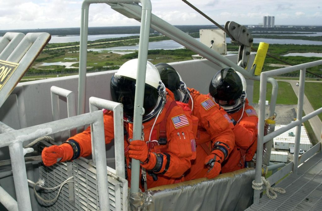 KENNEDY SPACE CENTER, FLA. -- As part of Terminal Countdown Demonstration Test activities, the STS-109 crew practices emergency exit from the Shuttle.  Seated in the slidewire basket at the 195-foot level of the Fixed Service Structure are Mission Specialists Richard Linnehan (reaching for the release lever), Michael Massimino and James Newman.   The TCDT also includes a simulated launch countdown.  STS-109 is a Hubble Space Telescope Servicing Mission, with goals to replace Solar Array 2 with Solar Array 3, replace the Power Control Unit, remove the Faint Object Camera and install the Advanced Camera for Surveys (ACS), install the Near Infrared Camera and Multi-Object Spectrometer (NICMOS) Cooling System, and install New Outer Blanket Layer insulation.  The 11-day mission will require five spacewalks to perform the tasks.   Launch of STS-109 aboard Space Shuttle Columbia is scheduled for Feb. 28, 2002 KSC-02pd0081