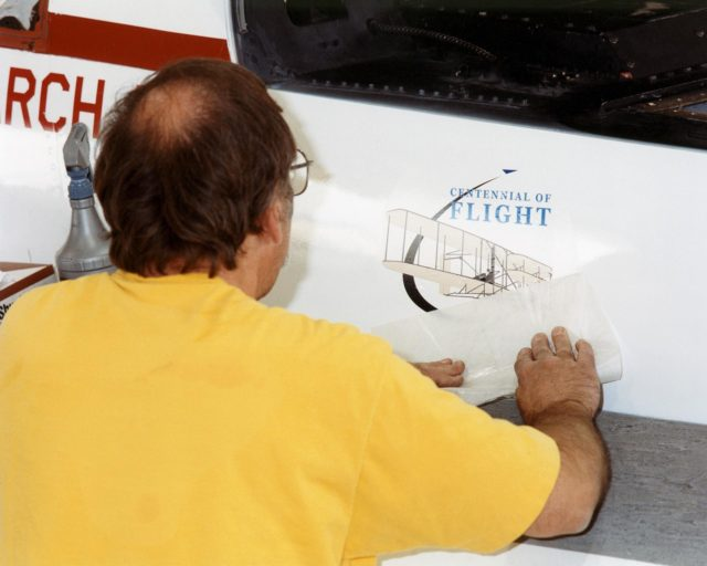 NASA aircraft technician Don Herman completes placement of the first official U.S. Centennial of Flight Commission logo on an aircraft, Dryden's Active Aeroelastic Wing (AAW) F/A-18. EC02-0061-1