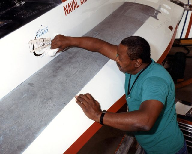NASA aircraft technician Donte Warren completes placement of the first official U.S. Centennial of Flight Commission logo on an aircraft, Dryden's Active Aeroelastic Wing (AAW) F/A-18. EC02-0061-2