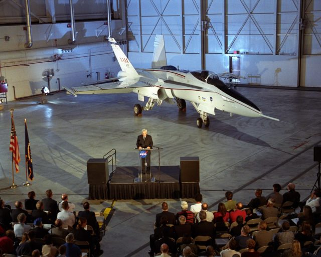 With the modified F/A-18 showcased behind him, Kevin Petersen, director of NASA Dryden Flight Research Center, addressed the audience attending the rollout ceremonies for the Active Aeroelastic Wing flight research project. EC02-0065-4