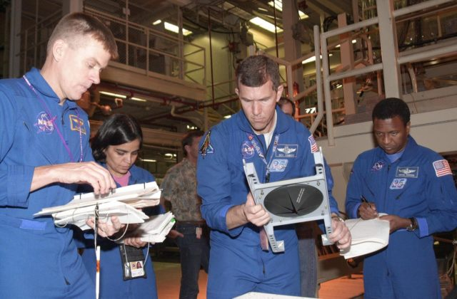 """KENNEDY SPACE CENTER, FLA. -- -- During Crew Equipment Interface Test activities, the STS-107 crew looks at flight equipment in the Orbiter Processing Facility. From left are Pilot William """"Willie"""" McCool, Mission Specialist Kalpana Chawla, Commander Rick Husband and Payload Commander Michael Anderson. STS-107 is a research mission, with the SHI Research Double Module (SHI/RDM), also known as SPACEHAB, as the primary payload, plus the Fast Reaction Experiments Enabling Science, Technology, Applications and Research (FREESTAR) that incorporates eight high priority secondary attached shuttle experiments.  STS-107 is scheduled to launch July 19, 2002 KSC-02pd0932"""